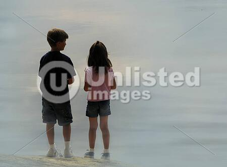 A boy and a girl surrounded by mist on a lake shore