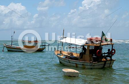 Small fishing boats on the green Atlantic Ocean in Brazil
