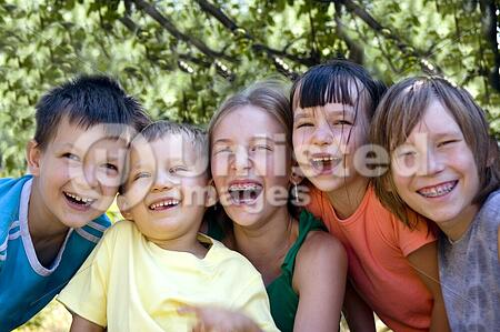 Smiling sisters and brothers in garden