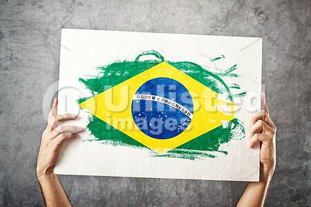 Brazil flag. Man holding banner with Brazilian Flag. Supporting national team, patriotism concept.