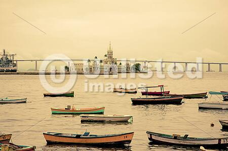 colourful boats and fort on harbor in Rio overlooking South Americas longest bridge