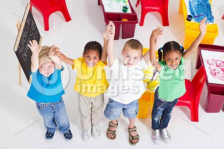 young group of preschool children in classroom looking up and holding hands