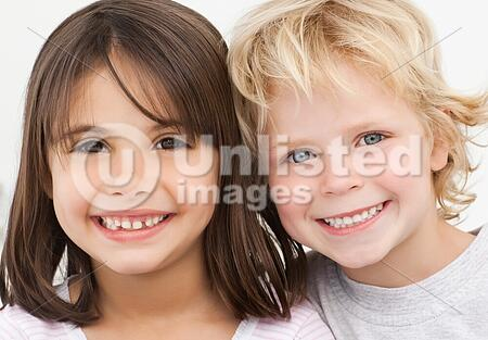 Portrait of two happy children in the kitchen at home