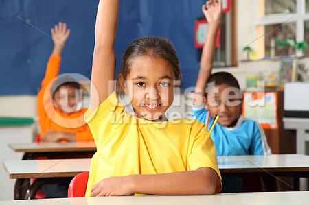 Three happy young primary school children signalling they know the answer with hands raised in class