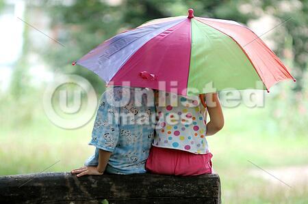An image of hildren sitting under umbrella
