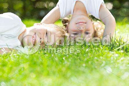 Happy children playing on green grass in spring park. Environment protection concept