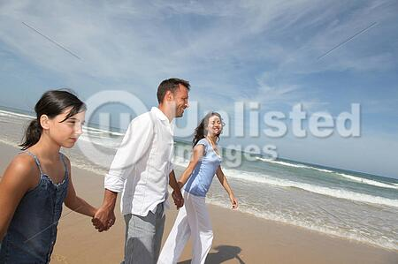 family walking by the beach in summer stock photos