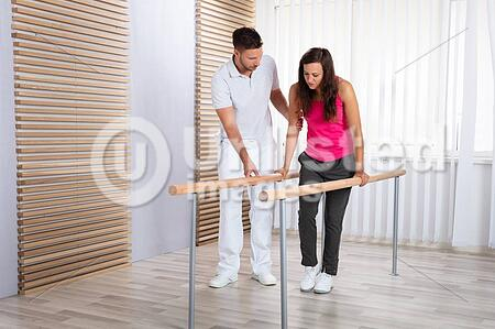 Therapist Assisting Patient While Walking In Clinic